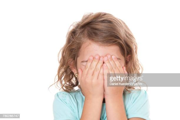 Girl Covering Face Against White Background