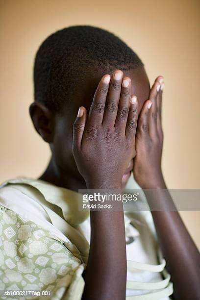 Girl (8-9) covering face, close-up
