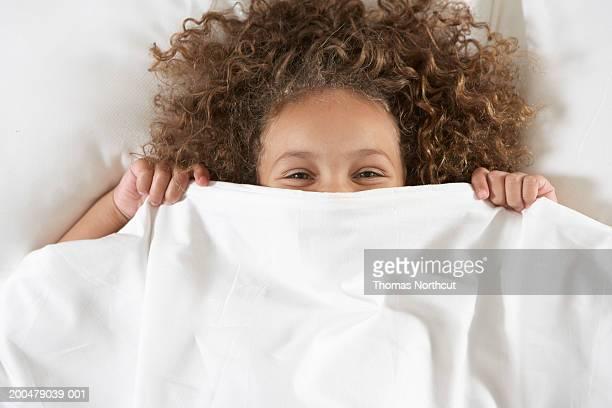 Girl (5-7), que abarquen cara con hoja en la cama, vertical