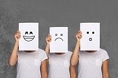 Emotions set. Girl hiding face behind signboard with drawn smileys. Collage of surprised, happy and sad emoticons.