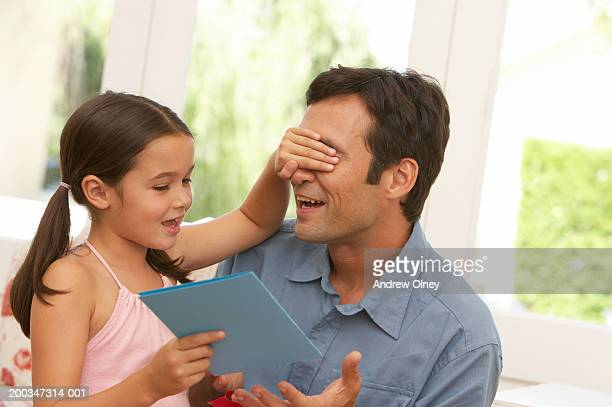 Girl (5-7) covering father's eyes, holding card