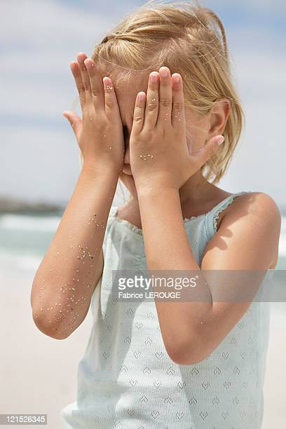 Girl covering her face with hands