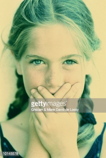 Girl (8-10) covering mouth with hands