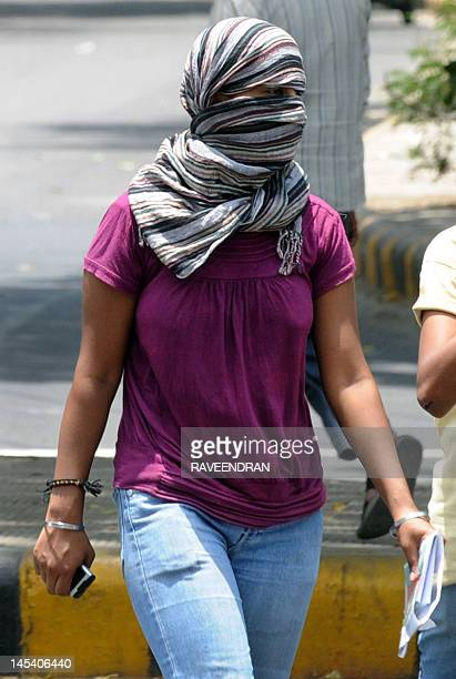 A girl covers her face from the sun as she walks along a street in New Delhi on May 29 2012 Heat wave conditions prevailed in the city and the...