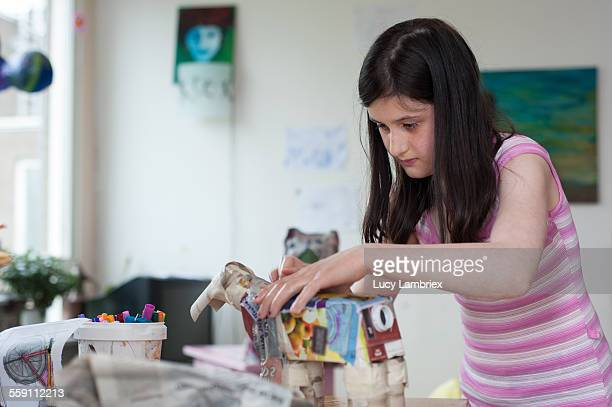 Girl crafting a horse from paper mache and waste