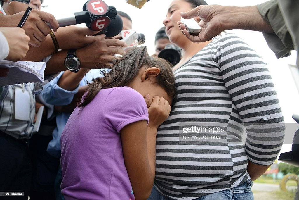 A girl cries as her mother speaks to the press upon arriving in San Pedro Sula, about 260 km north of Tegucigalpa, on July 14, 2014 after being deported from the United States. A first group of 120 deportees from Honduras, El Salvador and Guatemala who had crossed into the United States illegally were repatriated by plane to their countries -- most of them unaccompanied youths. US authorities have detained some 57,000 unaccompanied minors since October, twice the number from the same period a year ago, seeking to illegally cross into the US from Mexico. AFP PHOTO/Orlando SIERRA