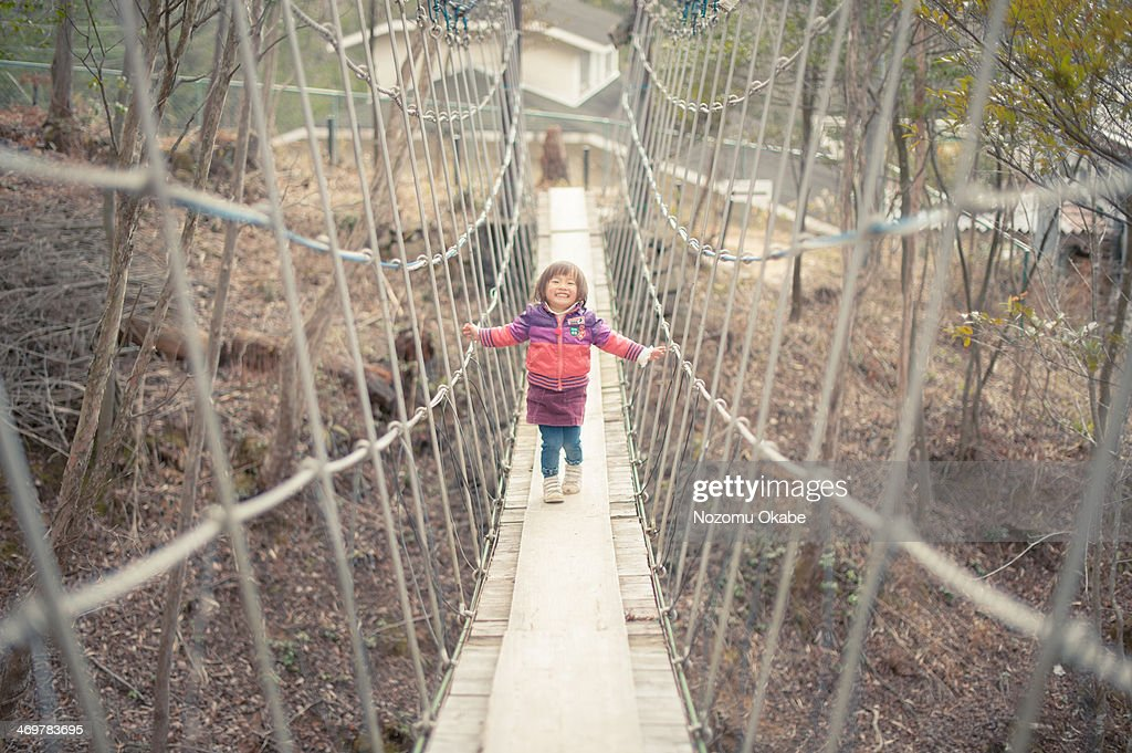 Girl crossing a suspension bridge : Stock Photo