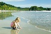 Girl (4-5) crouching at seashore, by waves