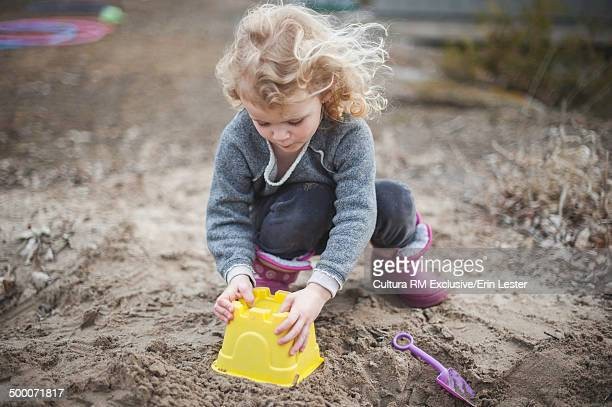 Girl crouching in sand making sandcastle with bucket
