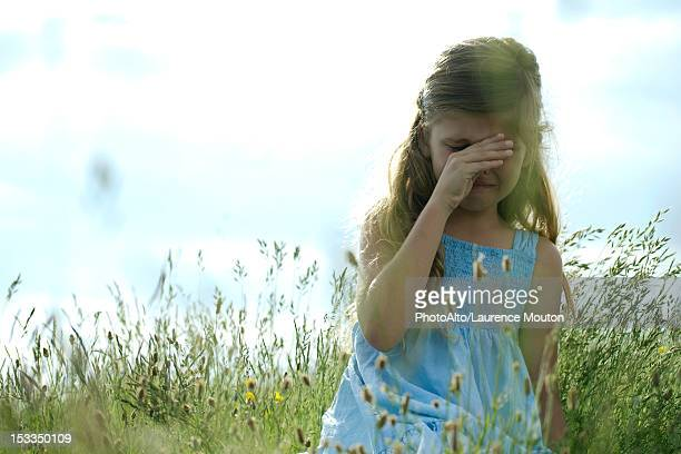 Girl crying in field, hand rubbing eyes