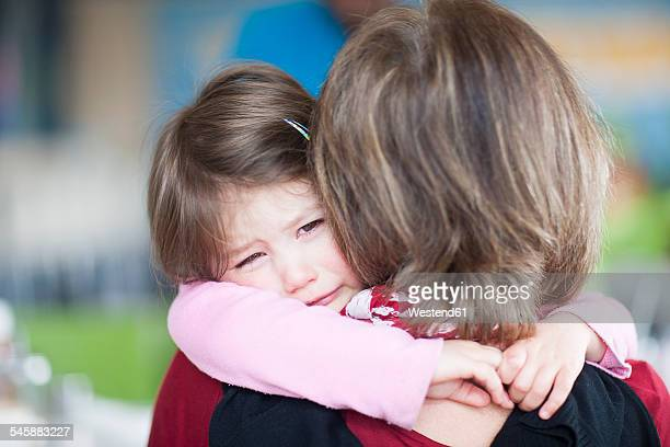 Girl crying in her grandmothers arms
