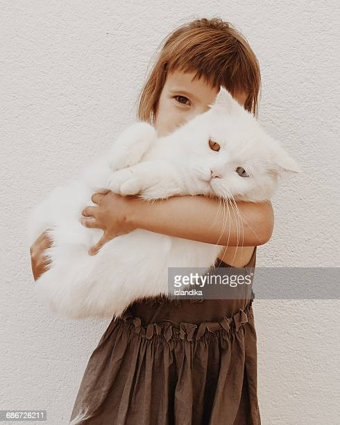 Girl cuddling her pet cat with different colored eyes