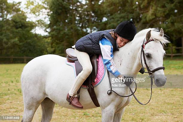 Girl cuddling her pony