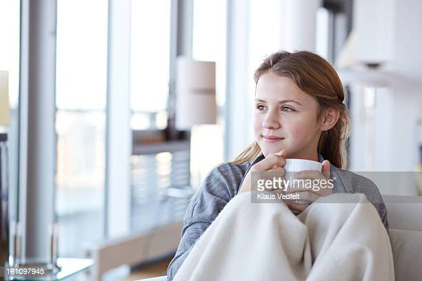 Girl cuddling w. blanket and tea looking out
