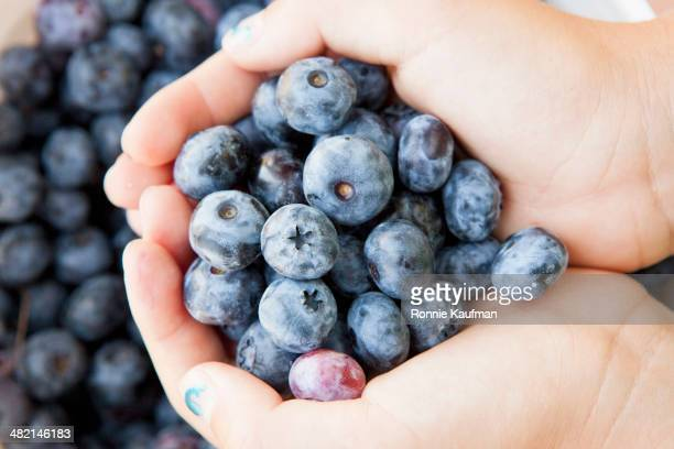 Girl cupping blueberries