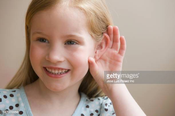 Girl cupping ear to hear better