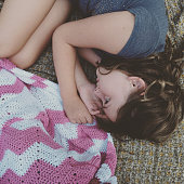 Girl Curled up with Crochet Blanket