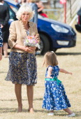 A girl curtseys for Camilla Duchess of Cornwall at Sandringham Flower Show on July 30 2014 in Sandringham England