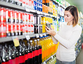 Girl customer looking for refreshing beverages in supermarket