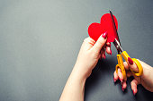 Girl cuts the red heart with scissors. The concept of breaking relations, quarrels and divorce. Betrayal of the othere. Loss of feelings for your loved one