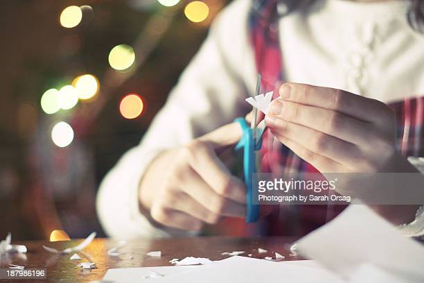 Girl cutting paper snowflakes