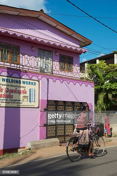 Girl cycling past colourful house