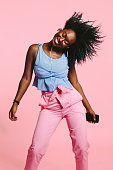 A young African American girl dancing, smiling, and listening to music on her headphones, holding cell phone with hair up in the air and eyes closed