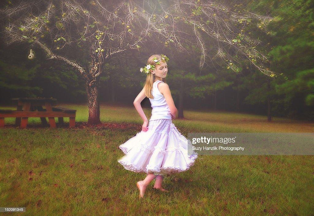 Girl dancing by apple tree : Stock Photo
