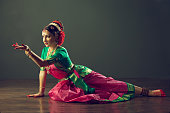 Girl, dressed in traditional national costume, dancing classical indian dance Kuchipudi. Emotional gestures of indian dance kuchipudi.