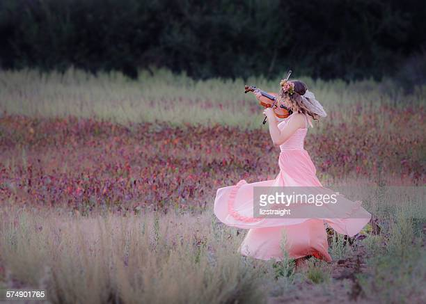 Girl dancing in a field whilst playing a violin