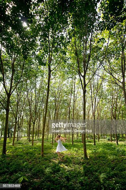 Girl dancing in a forest of rubber trees