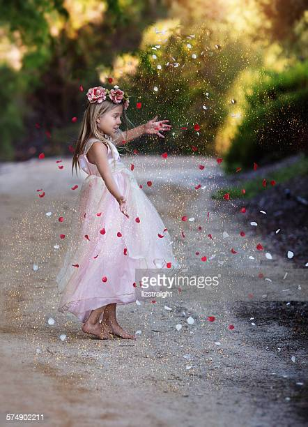 girl dancing on a dirt road surrounded by glitter and rose petals