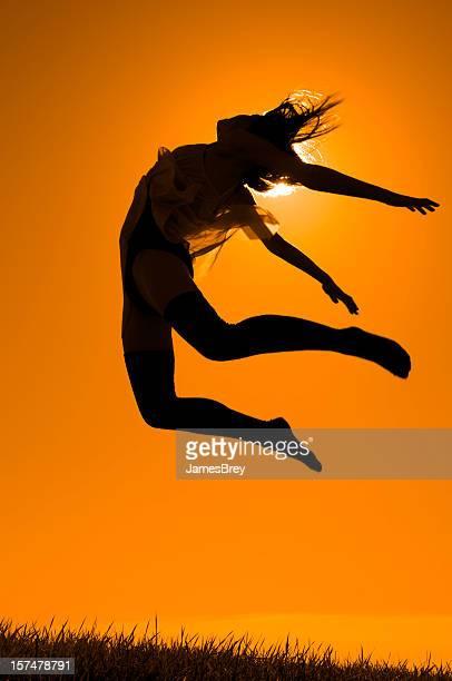 Fille danse sur une colline, sauter dans Golden Orange ciel