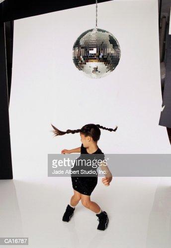 Girl (8-10) dancing under disco ball in studio : Stock Photo