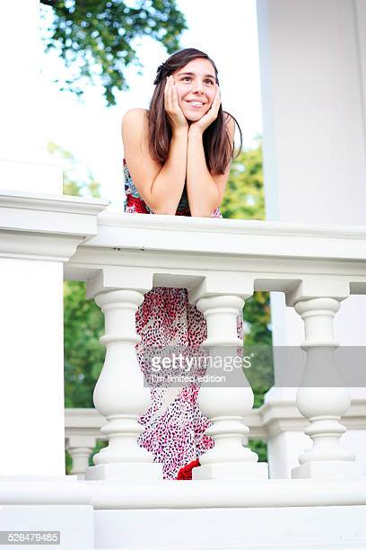 Girl daydreaming leaning on a white balcony