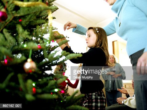 Girl (6-8) decorating Christmas tree with mother : Stock Photo