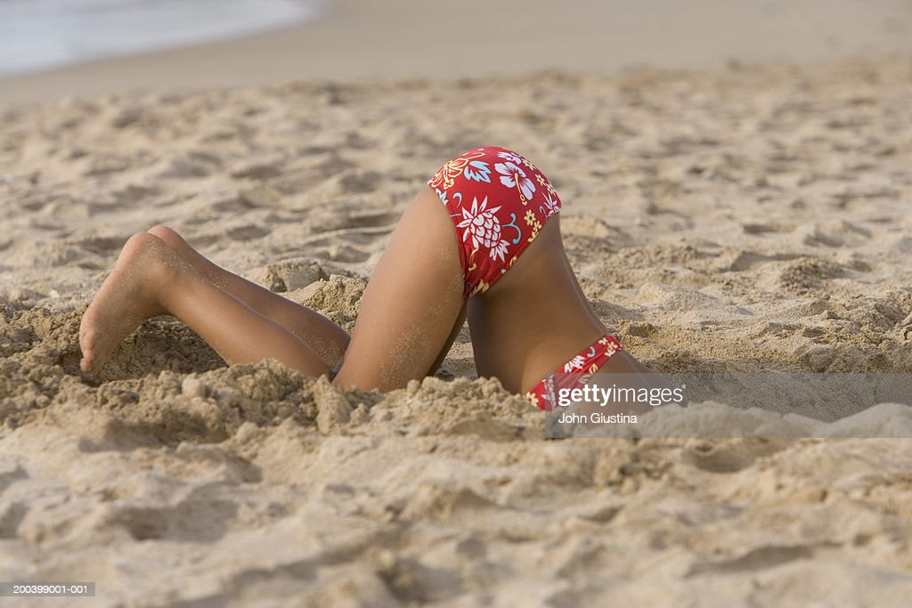 Girl (5-7) digging hole in sand on beach, side view, low section
