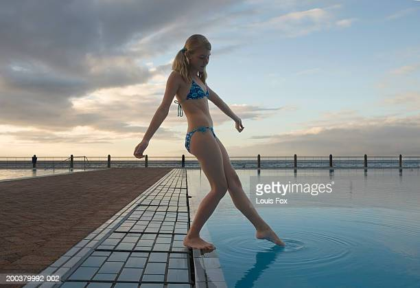 Girl (10-12) dipping toe in swimming pool, low angle view