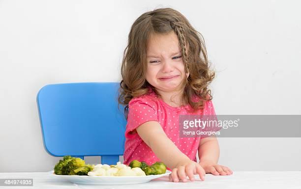 Girl disliking vegetables