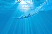 Underwater photograph of a female swimmer diving into the water with the sun beaming above