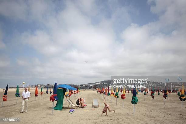 A girl does a cartwheel on the beach on July 21 2014 in Deauville northwestern France AFP PHOTO/CHARLY TRIBALLEAU