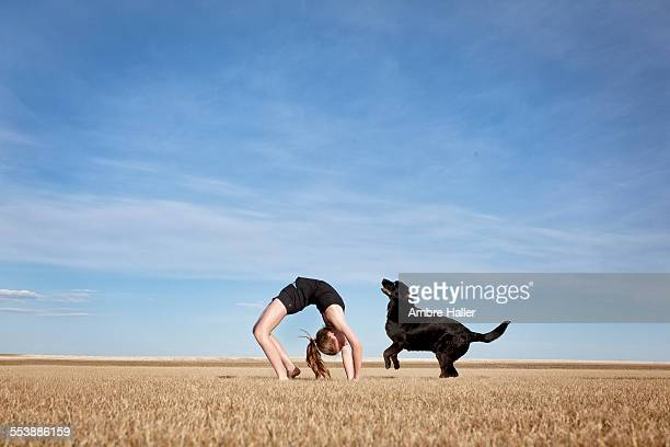 Girl doing a backbend with her dog
