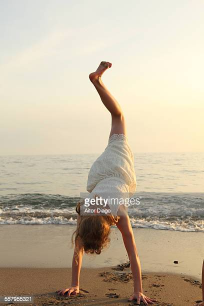 Girl doing a handstand at the beach. One leg up