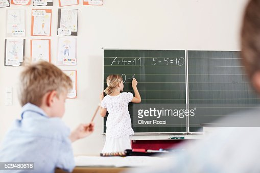 Girl doing arithmetic on blackboard : Stock Photo