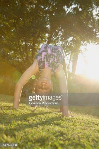 Girl doing backbend on grass : Stock Photo