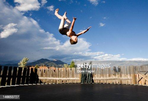 Girl doing backflip outdoors on a trampoline : Stock Photo