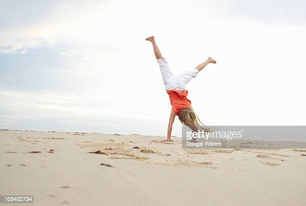 Girl doing cartwheel at beach.