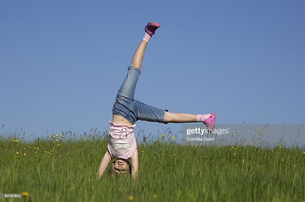 Girl doing cartwheel in meadow : Stock Photo