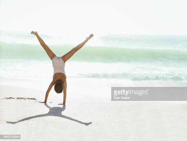 Girl doing cartwheel on beach
