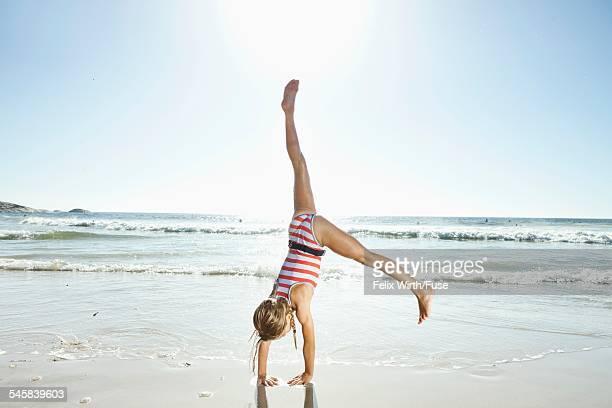 Girl (10-12) doing cartwheel on beach